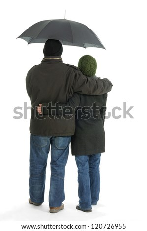 Couple hugging with umbrella in bad cold weather clothing backview