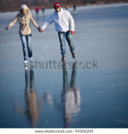 Couple ice skating outdoors on a pond on a lovely sunny winter day