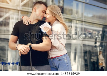 Couple in a airport. Beautiful blonde in a white jacket. Man in a black t-shirt #1487615939
