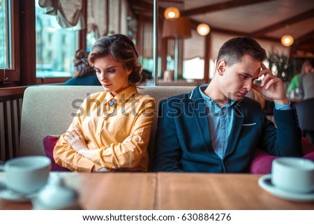 Couple in a bad mood sitting in restaurant