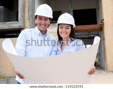 Couple in a construction site looking at their house design