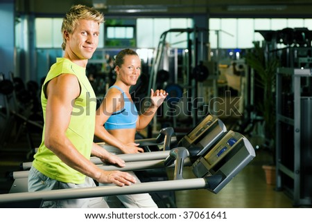 Couple in a gym working out on a treadmill