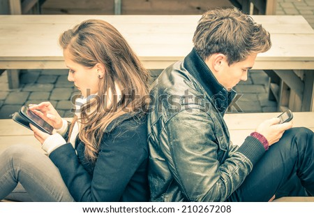 Couple in a modern common phase of mutual disinterest and sadness - Concept of apathy connected to the alienation fron new technologies - End of a love story  Stockfoto ©