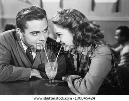 Shutterstock Couple in a restaurant looking at each other and sharing a milk shake with two straws