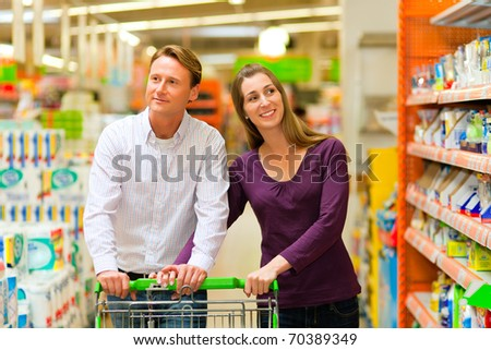 Couple in a supermarket shopping equipped with a shopping cart buying groceries and other stuff, they are looking for what they need