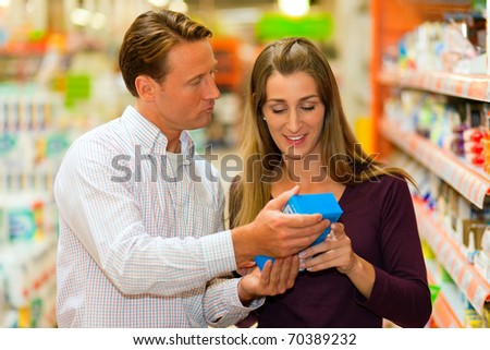 Couple in a supermarket shopping groceries and other stuff, they are looking for what they need