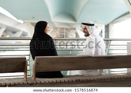 Couple in Abaya and Kanudra looking far with happy face. Smiling Arabs wearing cultural UAE clothing in the Middle East, Gulf countries. Arabic husband and wife concept