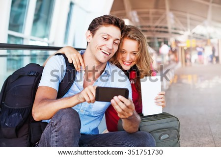 couple in airport using travel app on smart phone