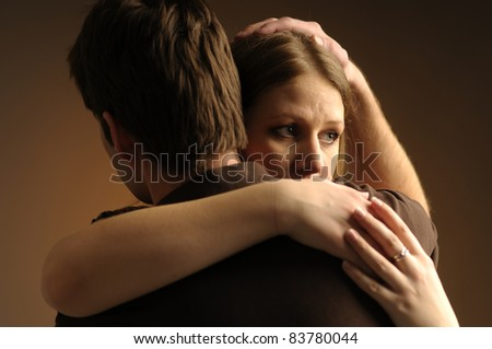 Couple in an embrace on an dark background - stock photo