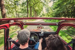 Couple in an ondtimer convertible, driving through the woods, carefree, enjoying the ride
