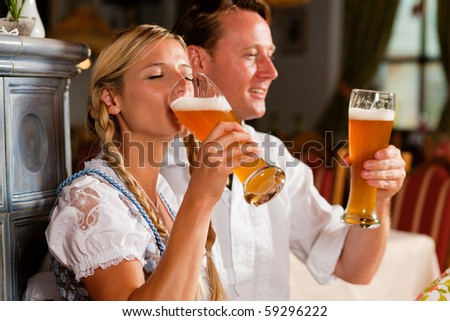 Couple in Bavarian Tracht drinking wheat beer in a typical pub
