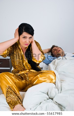 Couple in bed with woman awake and nervous because can't sleep and holding hands on ears while man sleeping and snoring