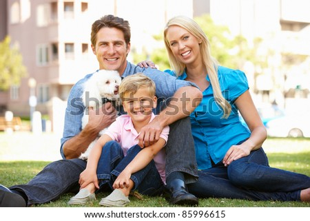 Couple in city park with young son and dog