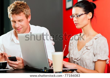 Couple in coffee shop with laptop and mobile; obviously they are working
