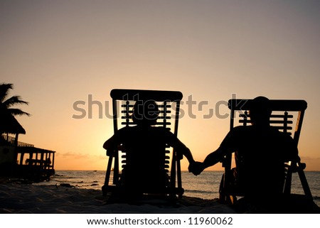 Couple in deckchairs holding hands at sunset