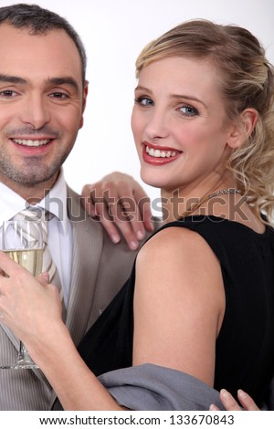 Couple in evening wear drinking champagne