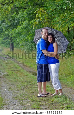 Couple in farm field with arms around each other holding an umbrella