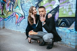 couple in fashionable outfit with french fries sitting near wall with graffiti on street