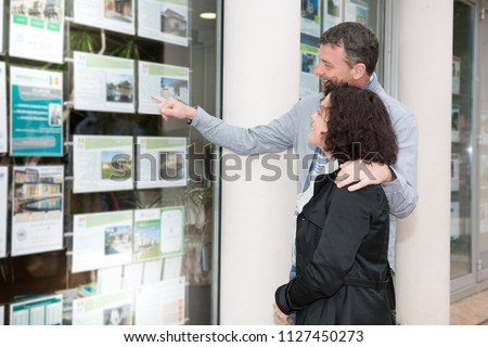couple in front of the window of a real estate agent #1127450273