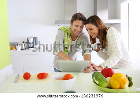 Couple in home kitchen looking for lunch recipe