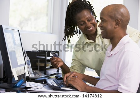 Couple in home office with credit card using computer and smiling