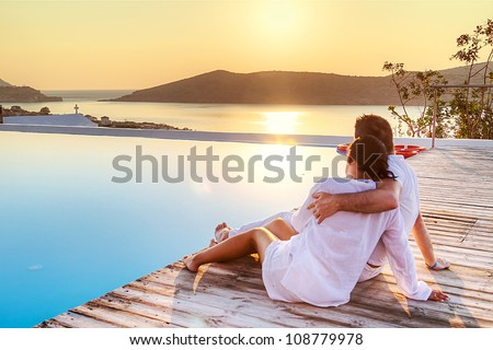 Couple in hug watching sunrise together - stock photo