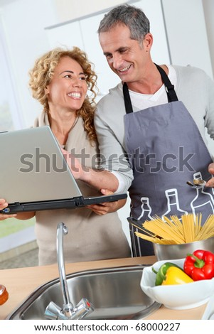 Couple in kitchen looking at recipe on internet - stock photo