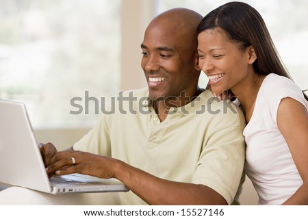 stock photo : Couple in living room using laptop and smiling
