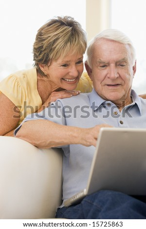 Couple in living room with laptop smiling