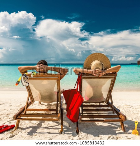 Couple in loungers on a tropical beach at Maldives #1085813432