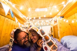 Couple in love and relationship have fun during a travel vacation with an old restored van to tiny house - van life concept for modern trendy people enjoying the freedom and the minimalism lifestyle