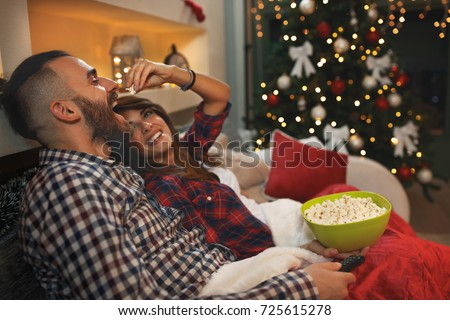 Couple in love at Christmas eve enjoy with popcorn while watching tv