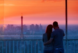 Couple in love at Paris admire Eiffel Tower at sunset