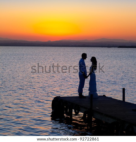 couple in love back light silhouette at lake sunset full length