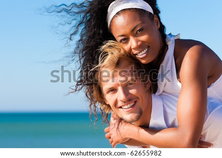 Couple in love - Caucasian man having his African-American woman piggyback on his back under a blue sky on a beach