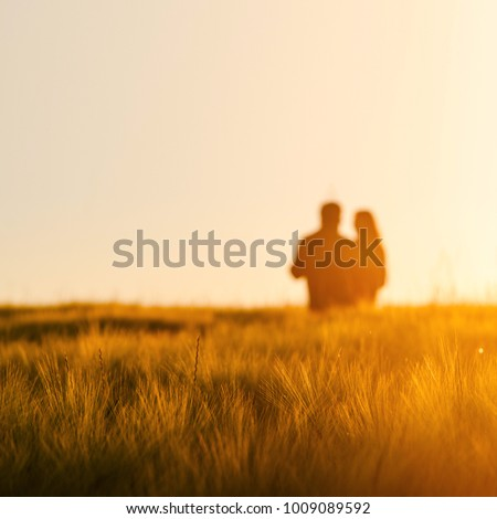 Couple in love dancing together in gold wheat field #1009089592