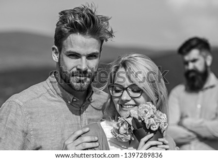 Couple in love dating while jealous bearded man watching wife cheating him with lover. Infidelity concept. Couple romantic date lovers bouquet flowers. Lovers hugs outdoor flirt romance relations. #1397289836