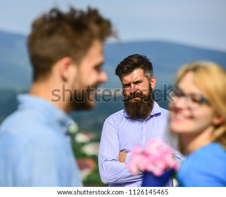 Couple in love dating while jealous husband fixedly watching on background. Lovers meeting outdoor flirt romance relations. Couple romantic date lover present bouquet flowers. Unrequited love concept. #1126145465