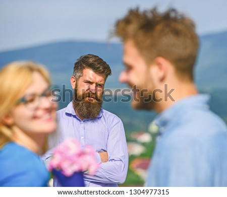 Couple in love dating while jealous husband fixedly watching on background. Lovers meeting outdoor flirt romance relations. Couple romantic date lover present bouquet flowers. Unrequited love concept. #1304977315
