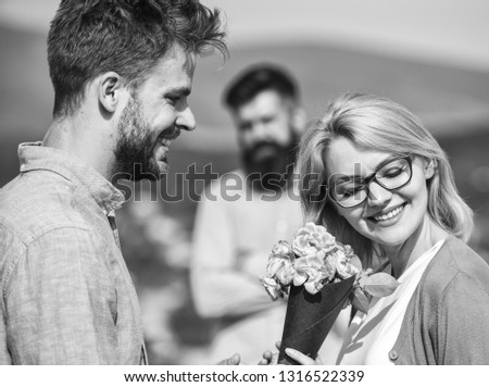 Couple in love dating while jealous husband fixedly watching on background. Lovers meeting outdoor flirt romance relations. Unrequited love concept. Couple romantic date lover present bouquet flowers. #1316522339