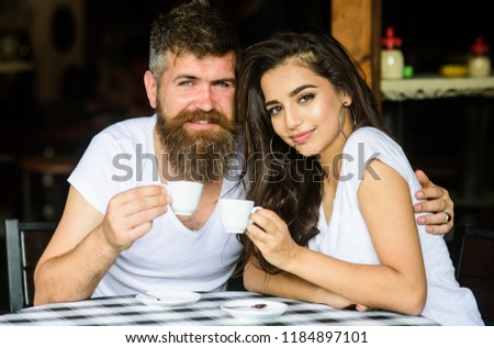 Couple in love drink black espresso coffee in cafe. Man with beard and attractive happy smiling girl hugs and drinking coffee. Pleasant family moment. Enjoy moment with cup of coffee drink. #1184897101