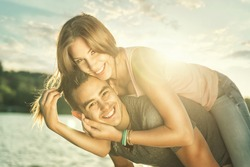 Couple in love embracing at the lake, sun flare