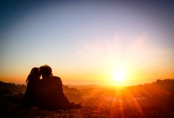 Couple in love enjoying tender moments during sunset at Twin Peaks in San Francisco - Emotional concept of relationship with travel boyfriend and girlfriends relaxing together