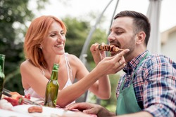 Couple in love enjoying their free time, making barbecue and having lunch in nature.