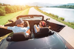 Couple in love getting into the convertible auto cabriolet and starting a trip. Couple honeymoon, traveling or vacation concept image.