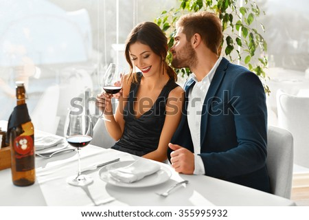 Couple In Love. Happy Romantic Smiling Elegant People Having Dinner, Drinking Wine, Celebrating Holiday, Anniversary Or Valentine\'s Day In Gourmet Restaurant. Romance, Relationships Concept.