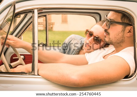 Couple in love having a rest during honeymoon vintage car trip - Hipster lifestyle traveling around the world with classic car - Young people enjoying happy moments of life - Warm retro filtered look