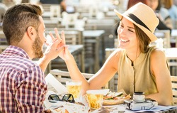 Couple in love having fun at beer bar on travel excursion - Young happy tourists enjoying tender moment at street food restaurant - Relationship concept with focus on girl face on warm bright filter