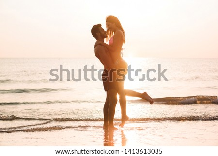 Couple in love having romantic tender moments at sunset on the beach - Young lovers enjoying summer vacation - Love, travel and relationship concept - Focus on bodies silhouette #1413613085