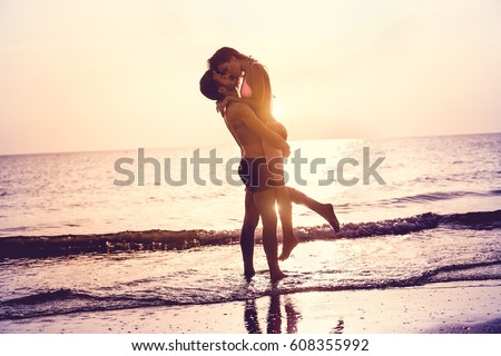 Couple in love having romantic tender moments at sunset on the beach - Young lovers having tender moments in summer vacation - Love concept - Soft focus on them - Matte filter with soft blue vignette